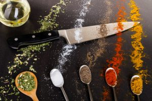 Ein Küchenmesser mit verschiedenen Gewürzen auf dem Kochtisch
