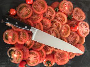 Das WIDDER Küchenmesser auf geschnittenen Tomaten, die auf dem Schneidebrett liegen